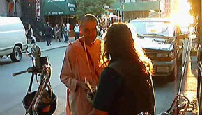 Kapindra Swami Distributing Books in New York City light in background