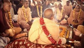 Srila Prabhupada viewed from behind preaching to devotees at pandal program in India
