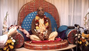 Srila Prabhupada playing kartals on red Vyassasana