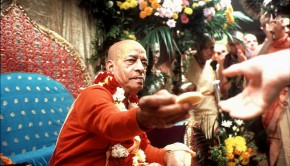 Srila Prabhupada distributing prasadam cookies from Vyassasana