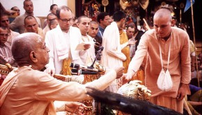 Srila Prabhupada hands disciple japa beads at initiation ceremony
