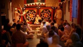 Srila Prabhupada sitting on platform in small room with devotees