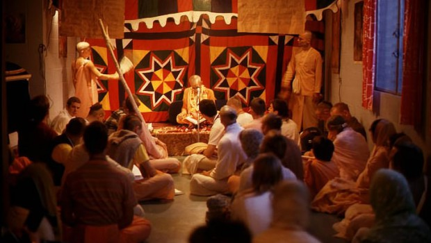 Srila Prabhupada sitting on platform in small room with devotees