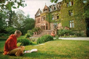 Devotee reading on grass outside Hare Krishna temple [castle] in Europe