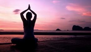 yoga teacher meditating at ocean sunrise