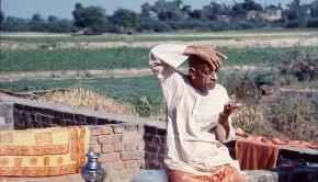 Srila Prabhupada applying tilak in the fields in India