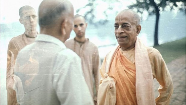 Srila Prabhupada speaks with Indian man while walking beside lake