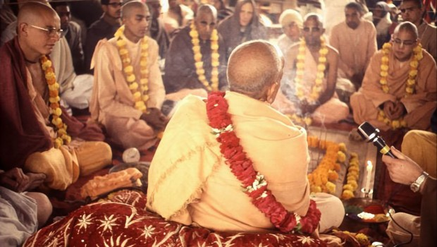 Srila Prabhupada viewed from behind preaching to devotees at pandal program in India