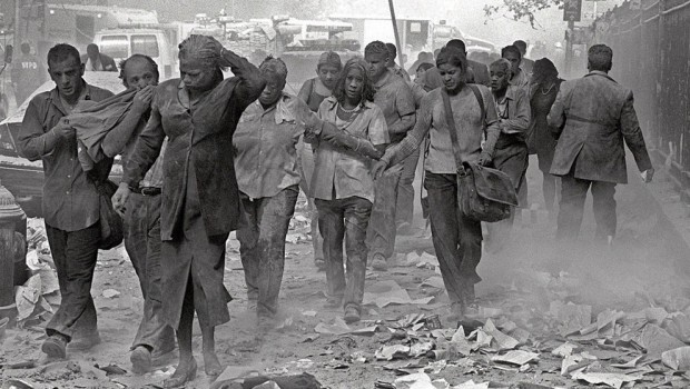 People covered in dust walk over debris near the World Trade Center in New York City on September 11 2001