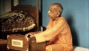 Srila Prabhupada playing harmonim next to bed