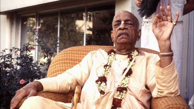 Srila Prabhupada sitting on chair outside preaching