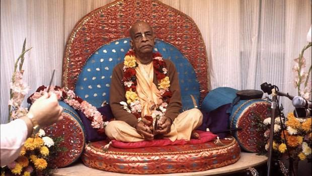 Srila Prabhupada playing kartals on red Vyassasana