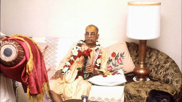 Srila Prabhupada sitting on couch holding rose