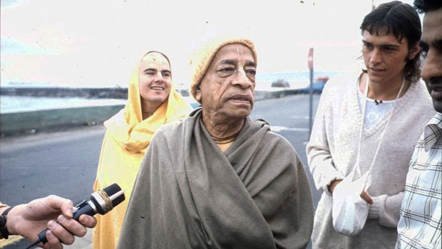 Srilla Prabhupada and disciples on road beside ocean