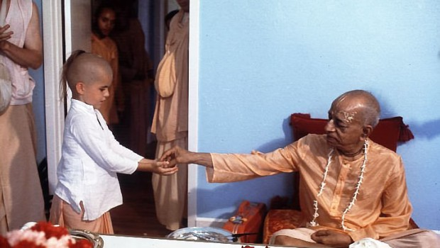 Srila Prabhupada distributing prasadam to a boy