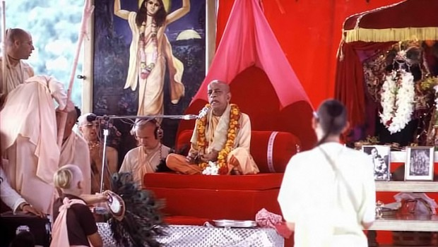 Srila Prabhupada sitting on Red Vyassasana Playing Kartals at New Vrindavan in pandal