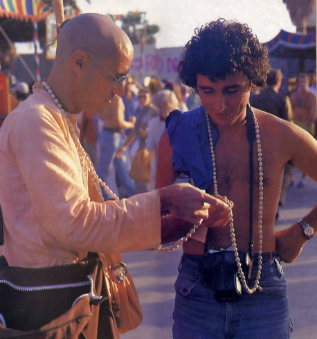 Hare Krishna Devotee Showing Young Man How to Chant Hare Krishna on Japa Beads